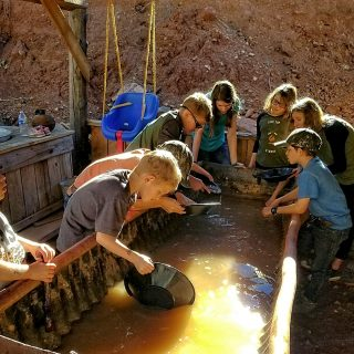 children eagerly gather at the sluice to pan for gold at the gold king mine and ghost town in jerome arizona