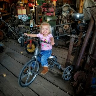 a youngster tries an old tricycle on for size