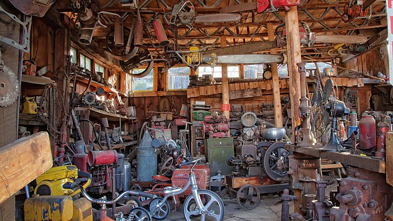 old chainsaws hang from the rafters and old outboard motors and tricycles can be seen